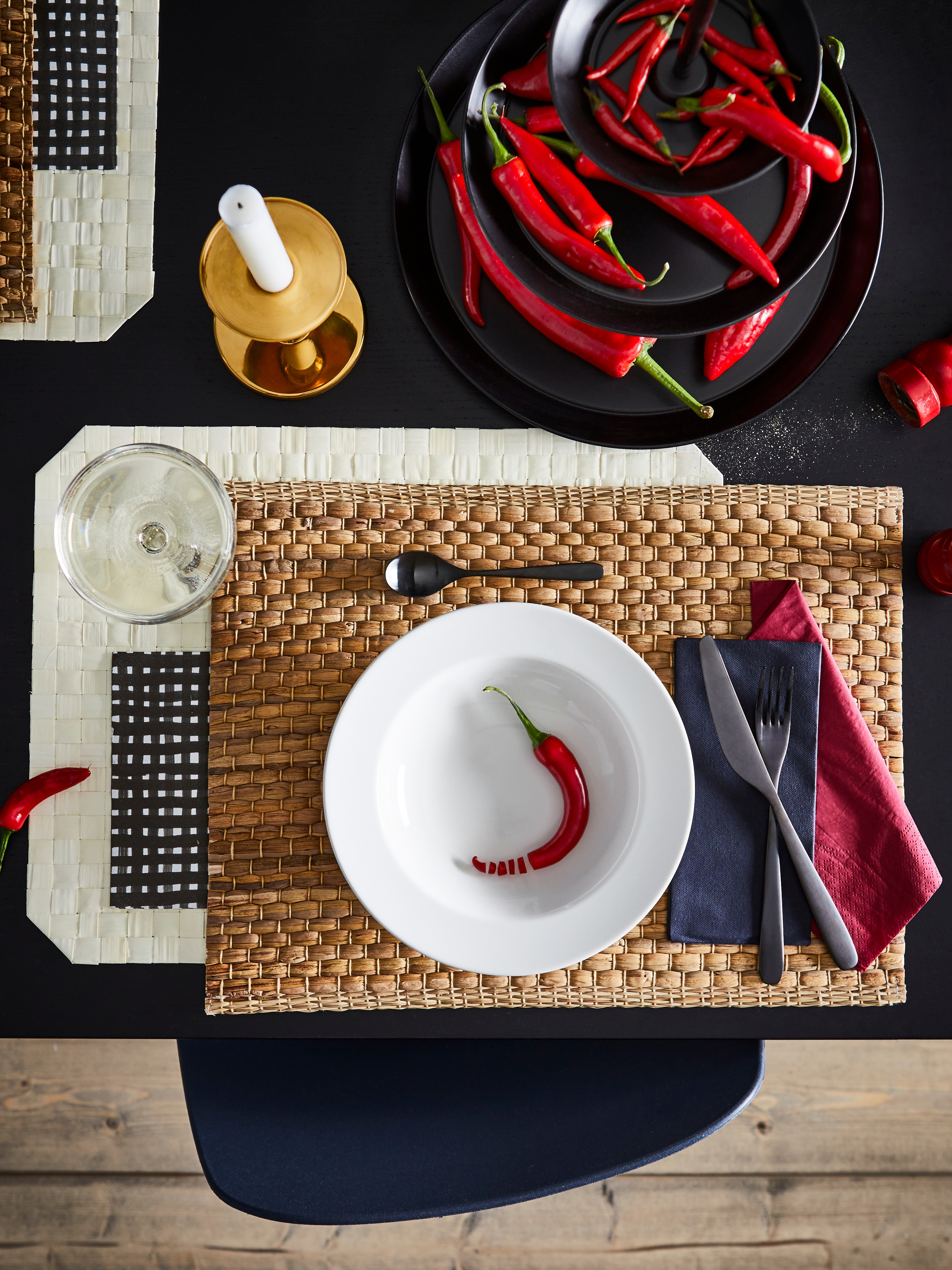 Place mat with VARDAGEN deep plate in off-white containing a red chili pepper, on a table with chilli peppers and tableware.