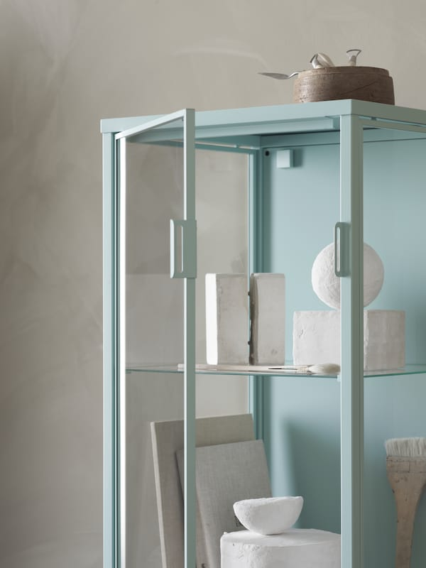 A light turquoise RUDSTA glass-door cabinet with an open door and filled with white ornaments stands in a minimalist space.