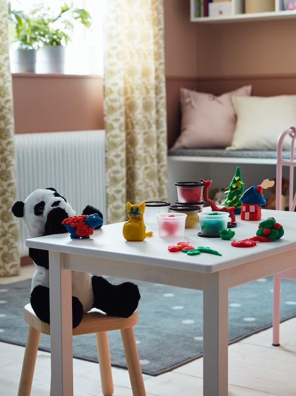 Et hvidt bord til børn, en sort og hvid pandabamse, modellervoks formet som en kat, en giraf, et hus og andre figurer.