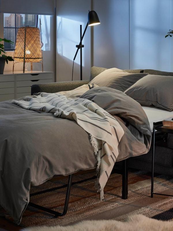 VIMLE bäddsoffa utbäddad till en säng med madrass, täcke och kuddar, i bakgrunden syns en stadssilhuett.