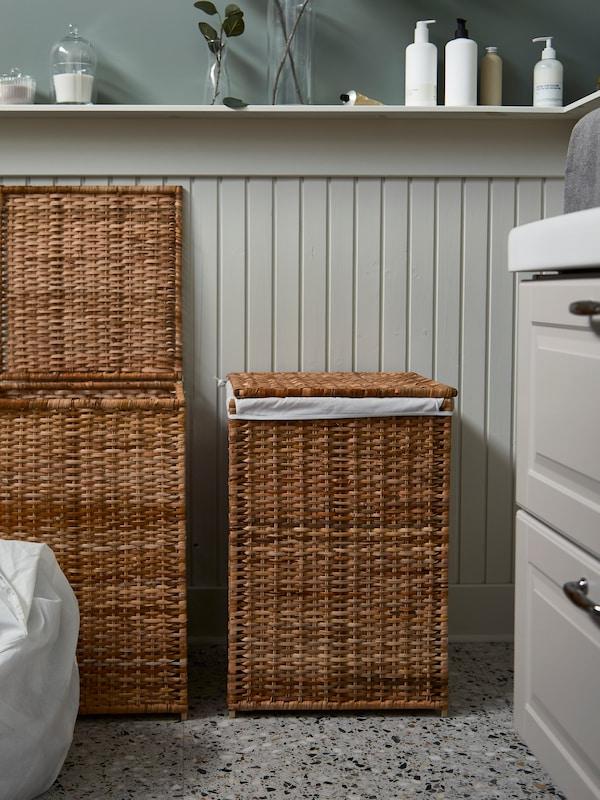Deux paniers à linge en rotin BRANÄS avec doublure en tissu. Un panier est ouvert et sa doublure contenant du linge est posée à côté.