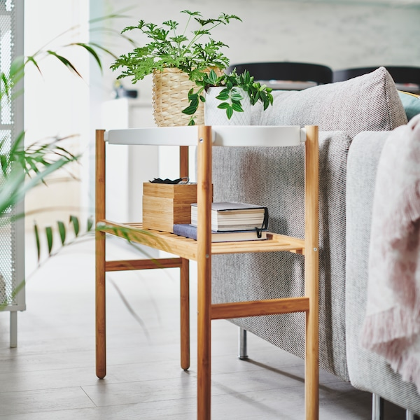 Za béžovo-hnedou pohovkou SÖDERHAMN sa nachádza bambusovo-biely stojan na kvetináče SATSUMAS sknihami, škatuľou aizbovou rastlinou.