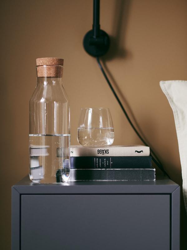 Carafe IKEA 365+ et verre DYRGRIP sur une table de chevet.