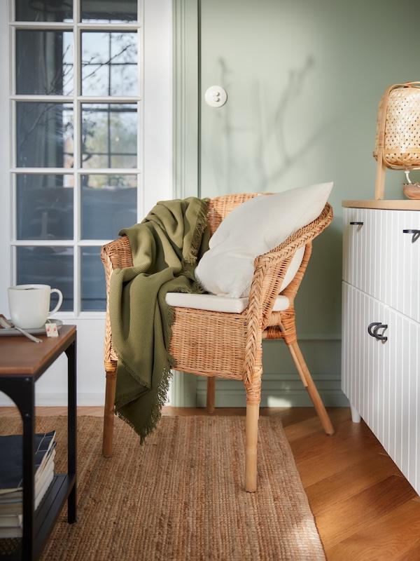 Cadeira de brazos de ratán, unha manta verde escura, coxíns, unha cunca de té sobre unha mesa para o café e unha alfombra de tecido plano.