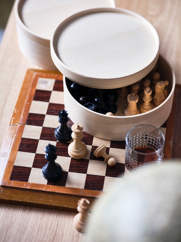 A MALLGRODA round storage box filled with chess pieces, standing on a chessboard.