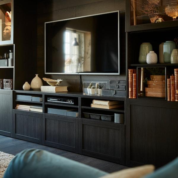 IKEA BESTÅ låg mörkbrun tv förvaring med lådor och skåp i ett mörkt vardagsrum med en tv ovanpå