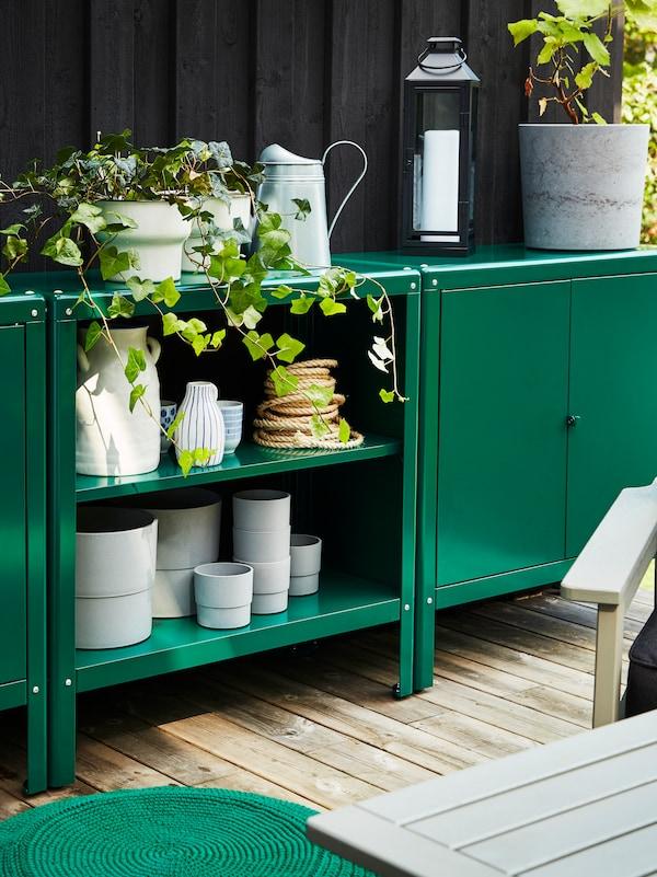 خزانتان ووحدة رفوف لون أخضر. أواني رمادية مخزنة بالداخل وإبريق سقي ونباتات من أعلى.