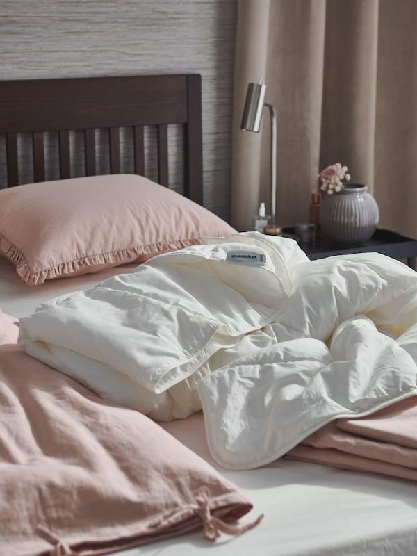 A bedroom with an IDANÄS bed get prepped for a linen change for spring with STJÄRNBRÄCKA duvet and KRANSKRAGE duvet sets.