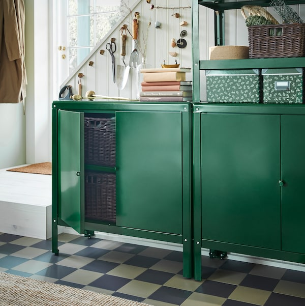 A hallway with KOLBJÖRN cabinet and shelving unit in green, holding baskets and boxes, with a jute rug on the floor.