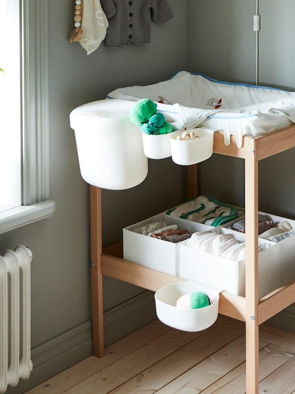 Un cambiador SNIGLAR con una funda de cambiador y cestas de almacenaje ÖNSKLIG acopladas al lateral con artículos de cuidado del bebé.