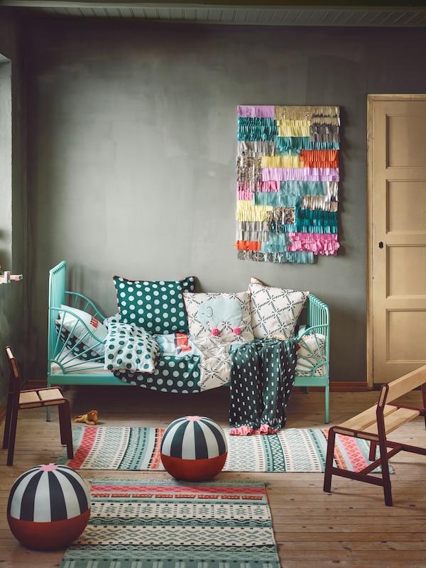Une chambre d'enfant ludique de style bohème avec un lit vert sur le mur du fond et beaucoup de textiles dessus. De petits tapis et des peluches sont posés sur le sol.