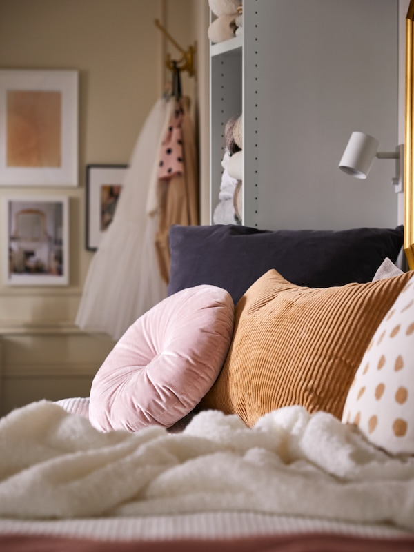 A round light pink KRANSBORRE cushion and various other cushions on a daybed with a white throw, beside a shelving unit.