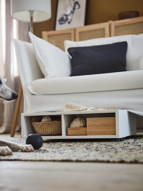 Ein weisser FREDVANG Bettkasten/Ablage mit Boxen und einem Korb unter einem Sofa, u. a. mit einem Teppich, einem Hund und einem Ball.