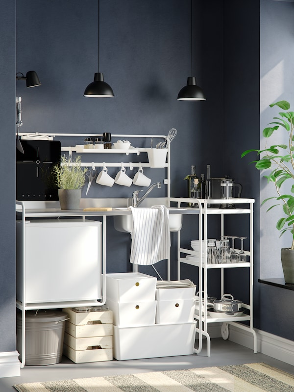 A white SUNNERSTA mini-kitchen with two pendant lamps against a dark grey wall, six white storage boxes underneath.