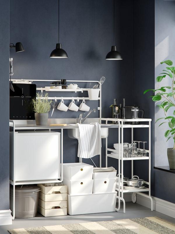 Hvidt SUNNERSTA minikøkken med 2 loftlamper ved en mørkegrå væg. Under køkkenbordet står der 6 hvide opbevaringsbokse.
