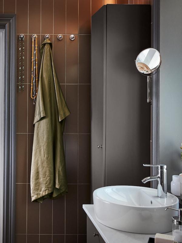 Conxunto de lavabo e moble de soporte en branco e gris escuro, armario alto gris escuro e cinco pomos con efecto cromado montados na parede.