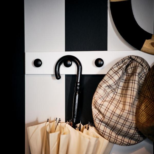 Verschiedene Outdoor-Gegenstände an schwarzen ENERYDA Knöpfen an einer weiß lasierten LURT Knopfleiste an einer schwarz-weißen Wand.