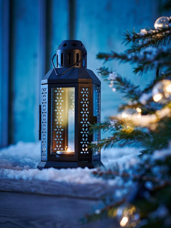 Et sneklædt landskab oplyst af en sort ENRUM lanterne af glas og stål til fyrfadslys ved siden af et grantræ med en UTSUND LED-lyskæde.
