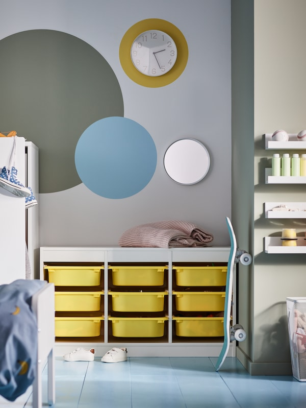 A children's room with a wall clock, a mirror, a skateboard and a white TROFAST storage combination with nine yellow boxes.