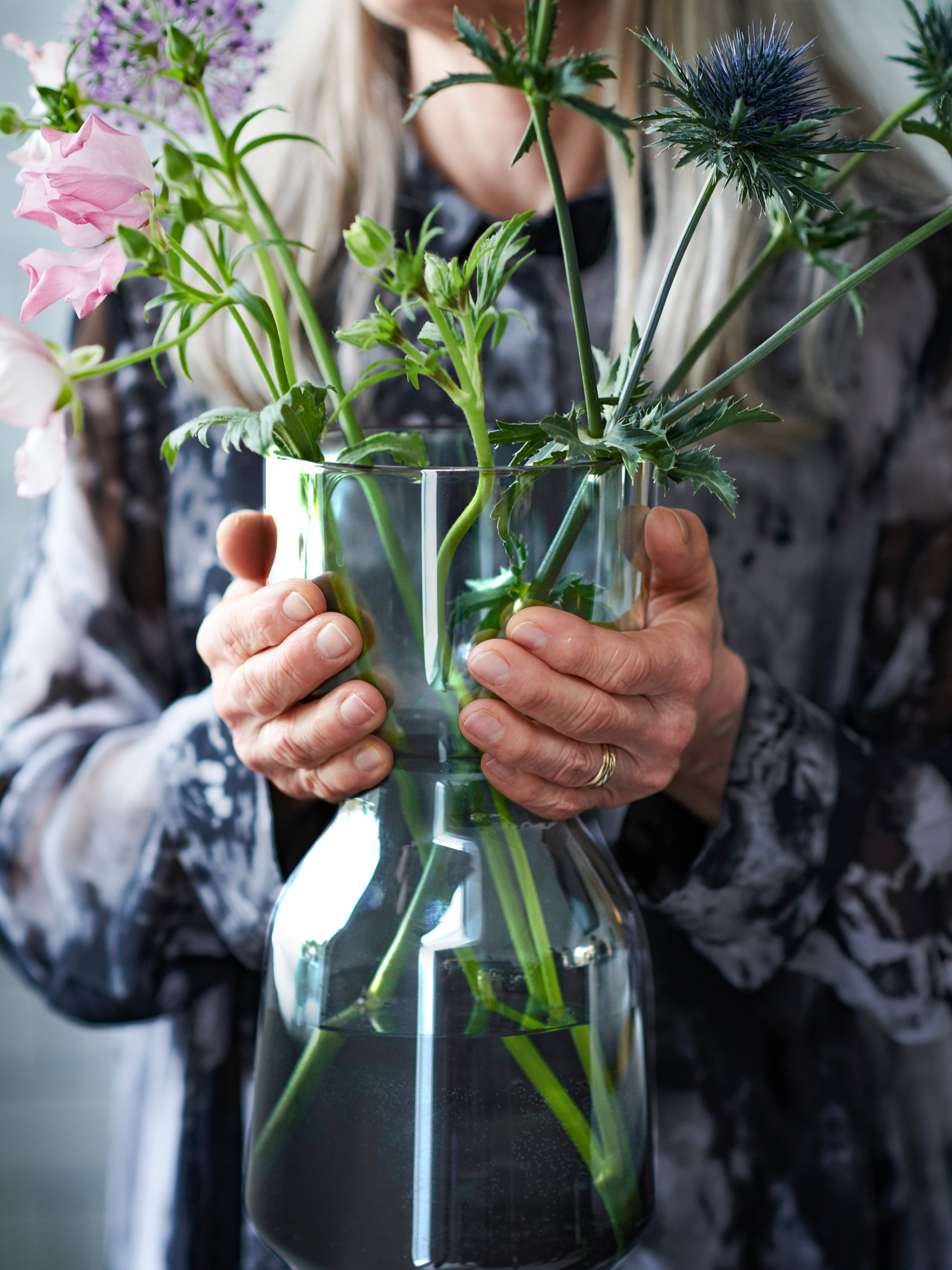 A person wearing a gold wedding band holds the wide waist of a light grey OMTÄNKSAM glass vase with fresh flowers.