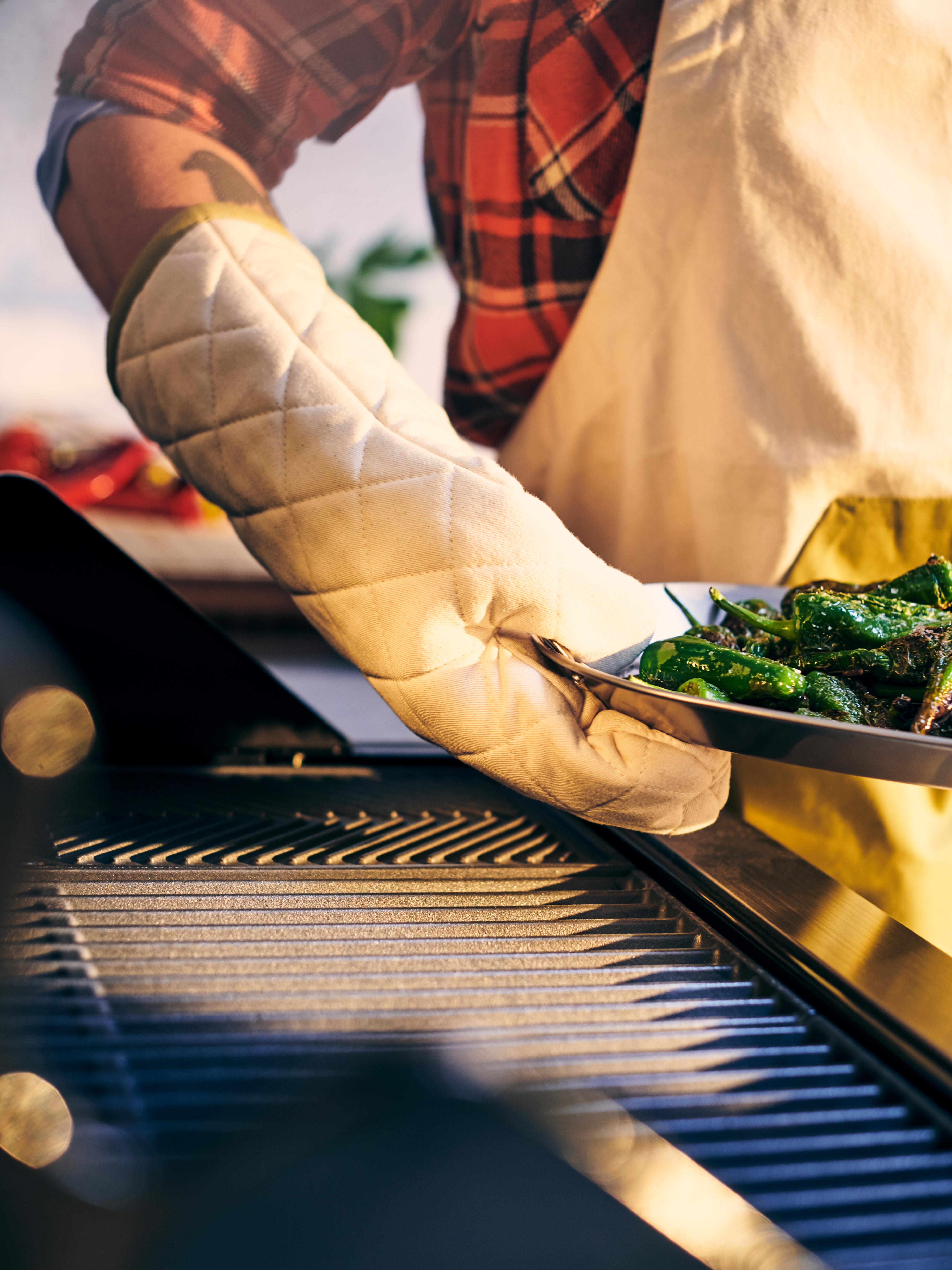 Un cuisinier porte des gants de cuisine GRILLTIDER et un tablier pour ramasser un plateau de légumes du barbecue à gaz GRILLSKÄR .