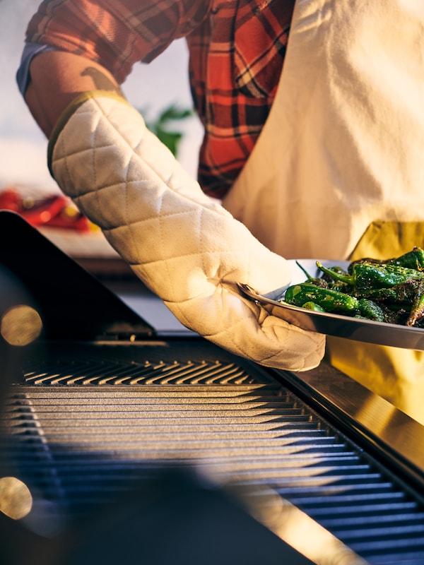 Gril KLASEN a chňapka držící grilovací podnos GRILLTIDER s grilovanými zelenými paprikami.