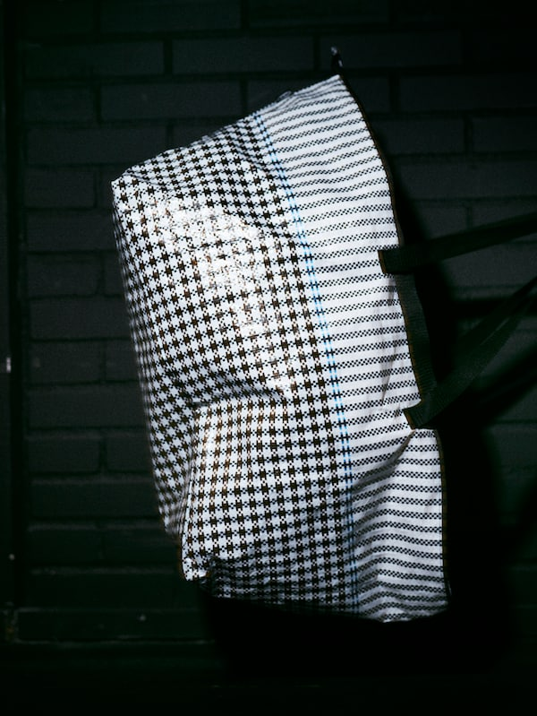 A roomy SAMMANKOPPLA bag with a black and white houndstooth pattern and a shiny texture in a dark room.