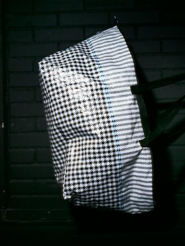 Una bolsa SAMMANKOPPLA grande con un estampado de pata de gallo de color blanco/negro y una textura brillante en una habitación oscura.