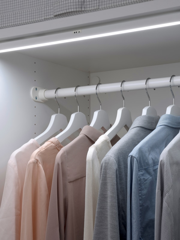 Shirts hanging by coat hangers from a rail in a white storage unit, with integrated lighting.