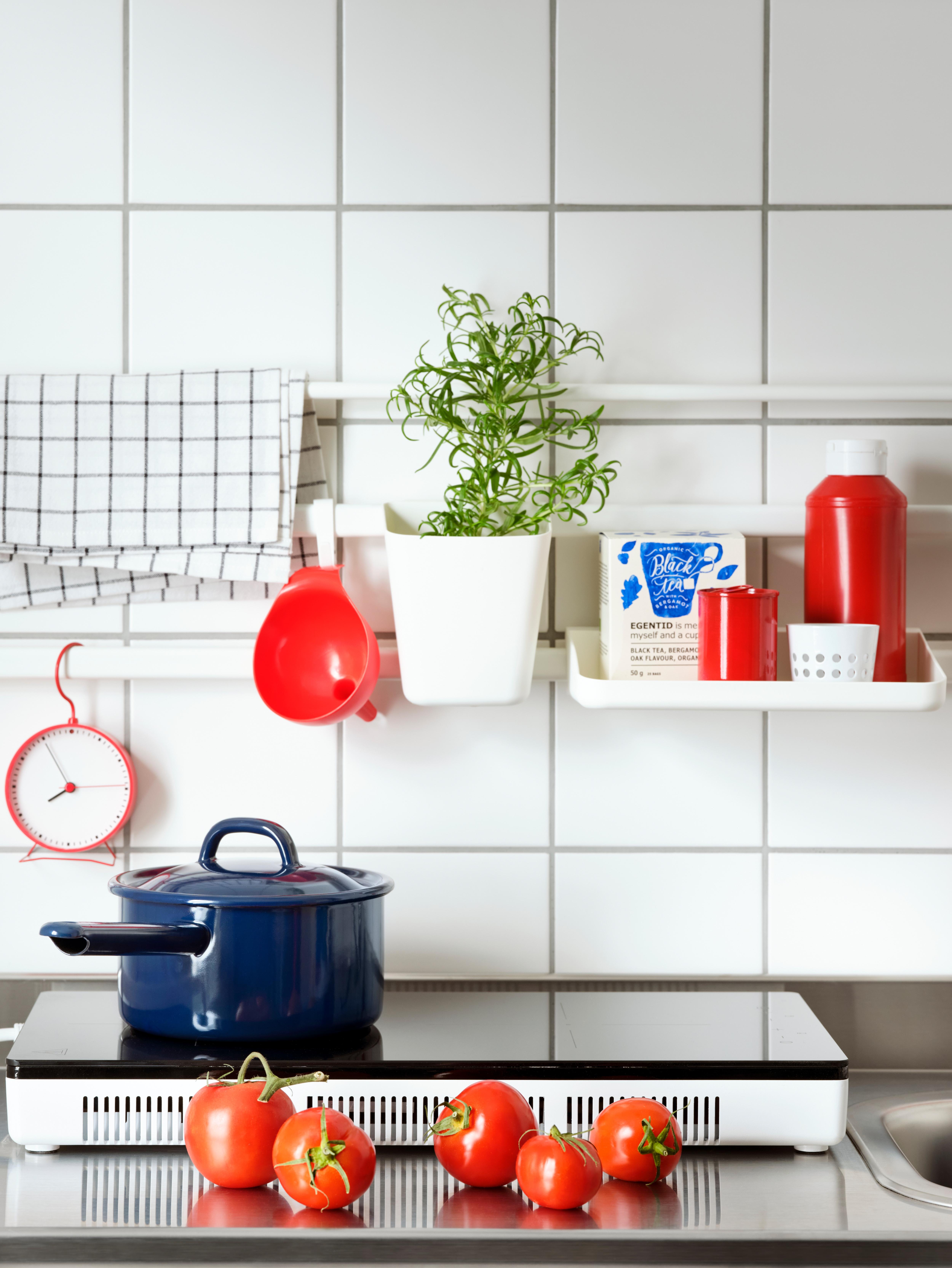 TILLREDA prijenosno indukcijsko kuhalište s plavom tavom, kuhinjski predmeti na bijeloj SUNNERSTA polici i posuda s biljem.