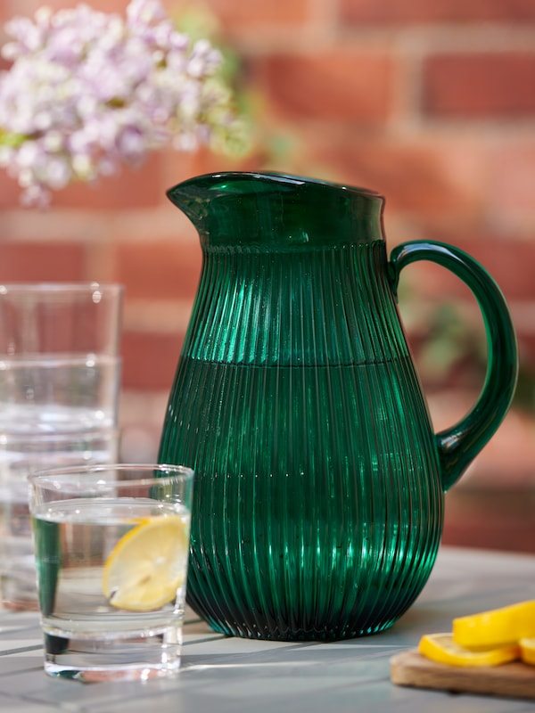 Stacked GODIS glasses and a green SÄLLSKAPLIG glass jug on a garden table standing in front of a sunlit brick wall.
