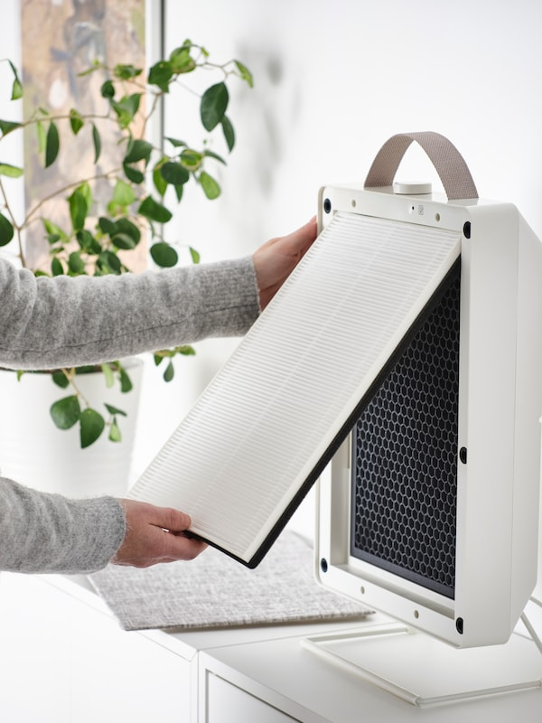 A person removing the particle filter from a white FÖRNUFTIG air purifier that is standing on a white chest of drawers.