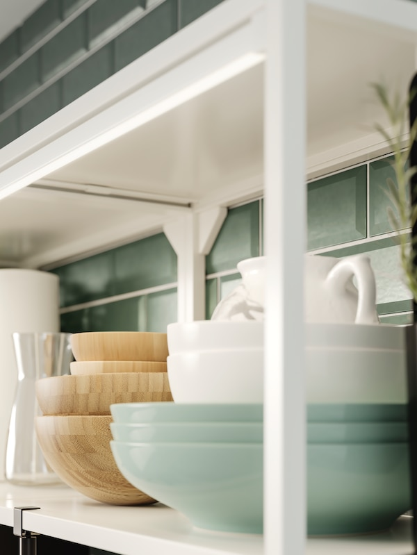 A white shelving unit holding bowls and dishes in wood and green and white porcelain, plus integrated lighting.