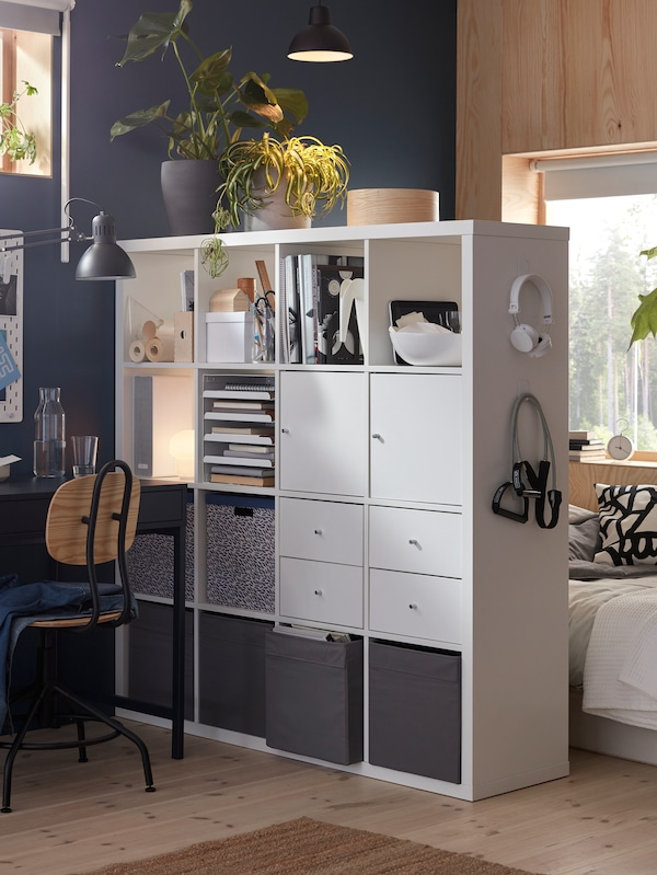 A room divided with a white KALLAX shelving unit with four inserts and DRÖNA boxes, creating a sleep zone and a workspace.
