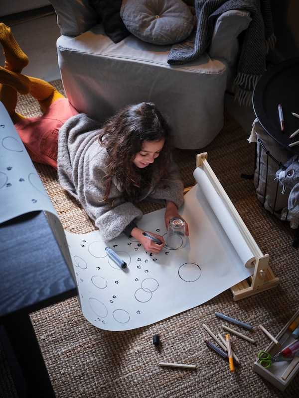 Allongée sur le plancher, une jeune fille colorie sur un rouleau de papier à dessin MALA.