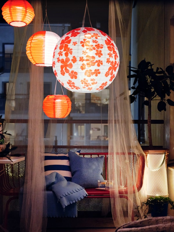 A balcony at night with several SOLVINDEN LED solar-powered outdoor lamps, a BRUSEN outdoor sofa with cushions and a throw.