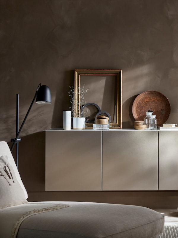 Wall-mounted white BESTÅ cabinets with a plant, frames, vases and diverse items on top. Beside is a black floor lamp.