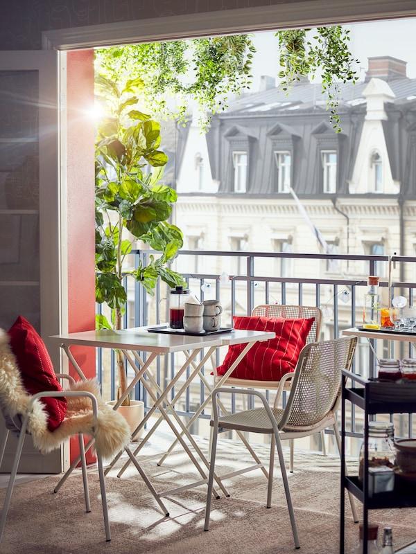 TORPARÖ jedilna miza in stoli z rdečimi blazinami stojijo na pol poti med dnevno sobo in odprtim balkonom.