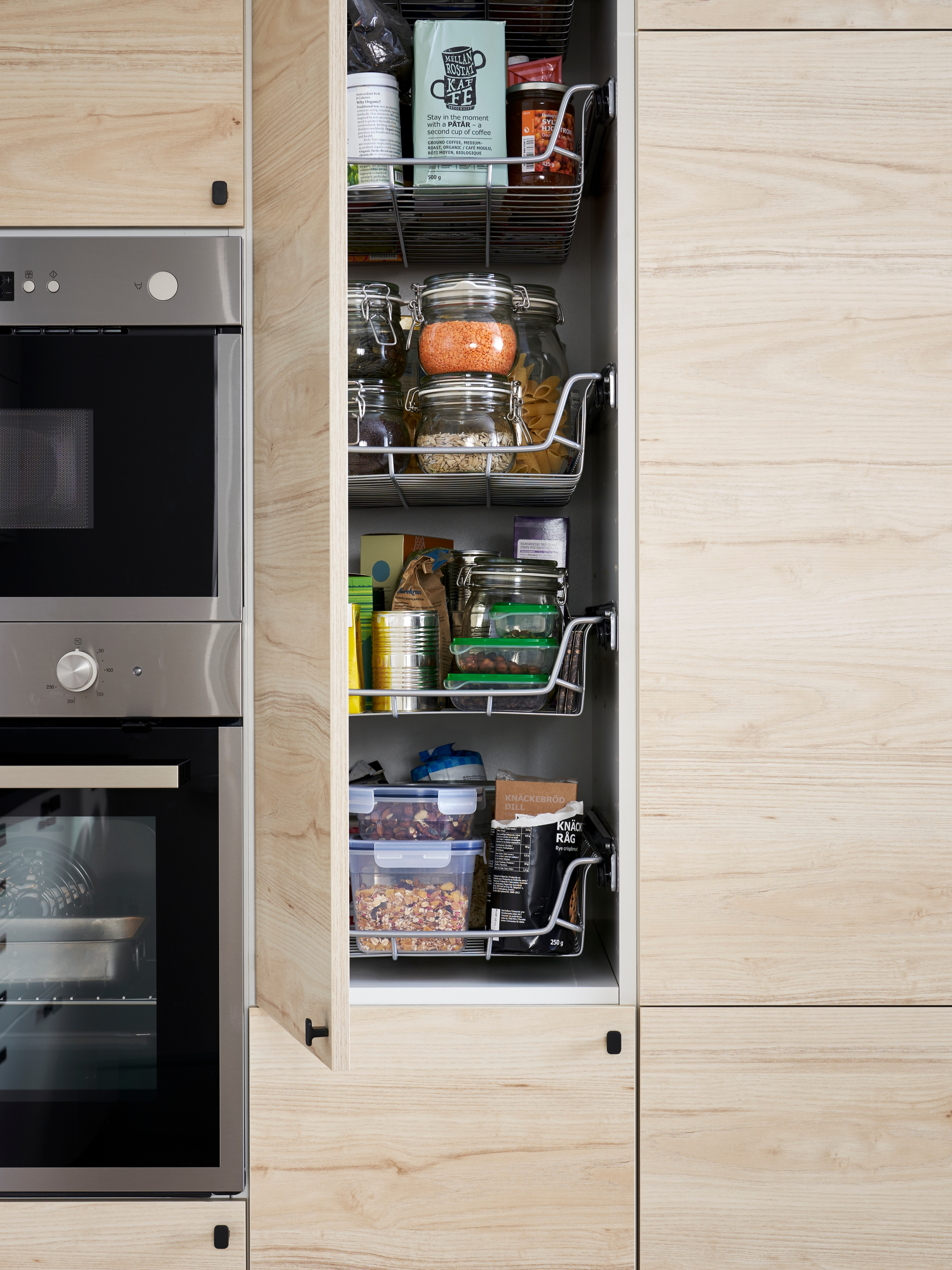 A kitchen with a high, ash effect cabinet door open to show UTRUSTA wire baskets filled with different foods and containers.