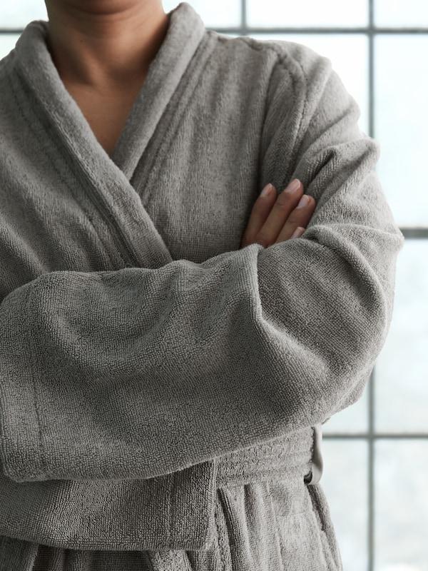 En kvinde står foran et badeværelsesvindue i en grå ROCKÅN badekåbe med armene foldet over brystet.