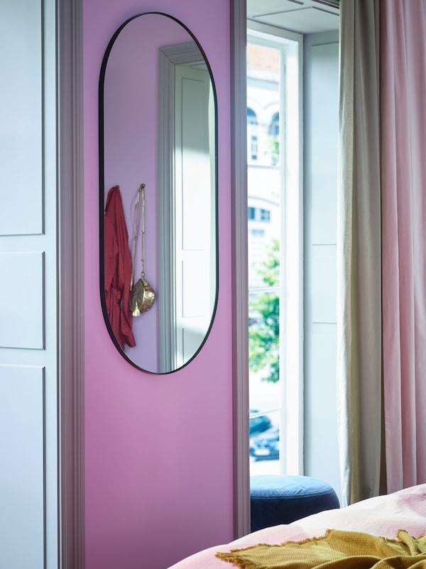 Fekete keretes, falra szerelt LINDBYN tükör egy keskeny falon két ablak között, bézs és rózsaszín függönyökkel.