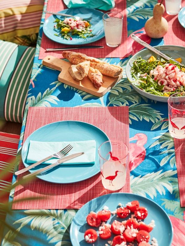 O masă este aranjată pentru prânz cu farfurii FARGRIK turcoaz, suporturi de farfurii SNOBBIG roșu deschis și o față de masă SOMMARLIV.