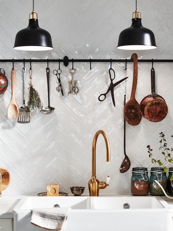 Tyč FINTORP s háčky připevněná nad umyvadlem. Na ní  jsou zavěšené  bylinky, kuchyňské náčiní a ozdobné předměty.