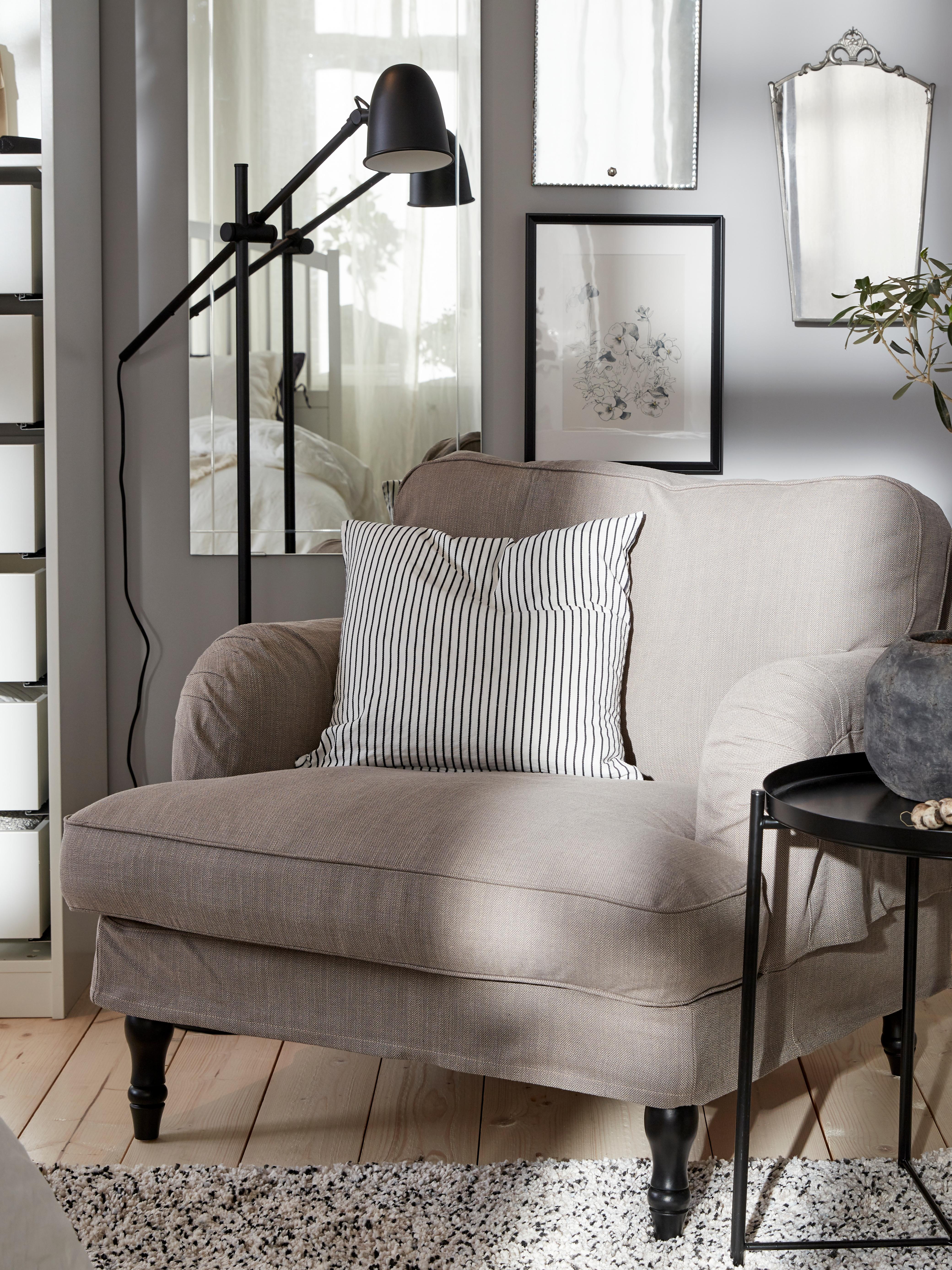 Camera da letto con poltrona STOCKSUND grigio-beige con seduta ampia e bassa e braccioli arrotondati, accanto a una lampada da terra nera e a un tavolino vassoio.