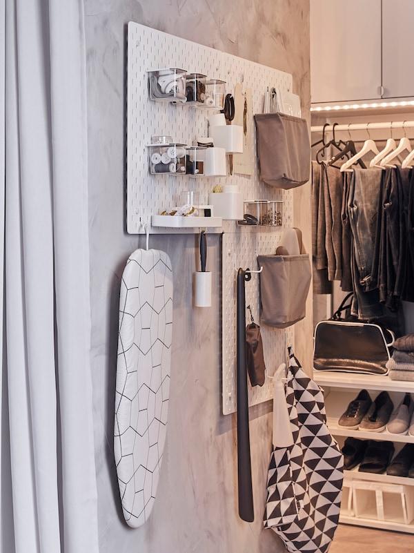 Die SKÅDIS Lochplatten und Zubehör wie z. B. Haken hängen hier an einem schmalen Wandteil. Mit ihrer Hilfe werden Kleiderpflegeprodukte organisiert und aufbewahrt.
