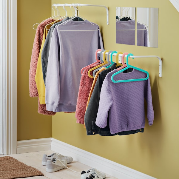 MULIG clothes racks hang in a bright hallway with LOTS mirrors placed at head height.