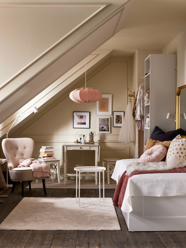 A bright room with a daybed, a beige rug, a white GLADOM tray table, a white shelving unit, beige armchair and pink pendant lampshade.
