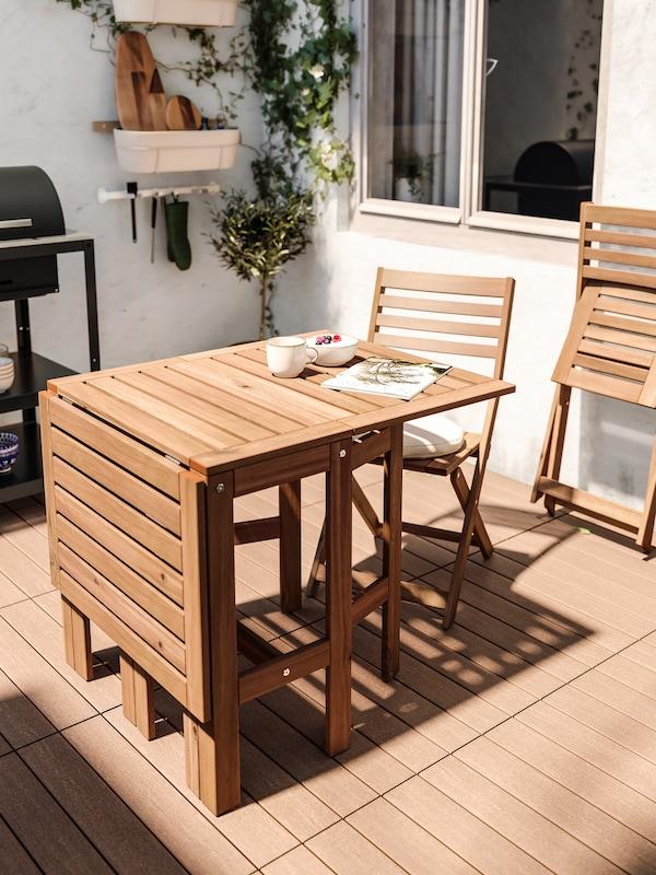 ÄPPLARÖ brunlaserat bord och två klappstolar står på en solig uteplats omgiven av vita stenväggar.