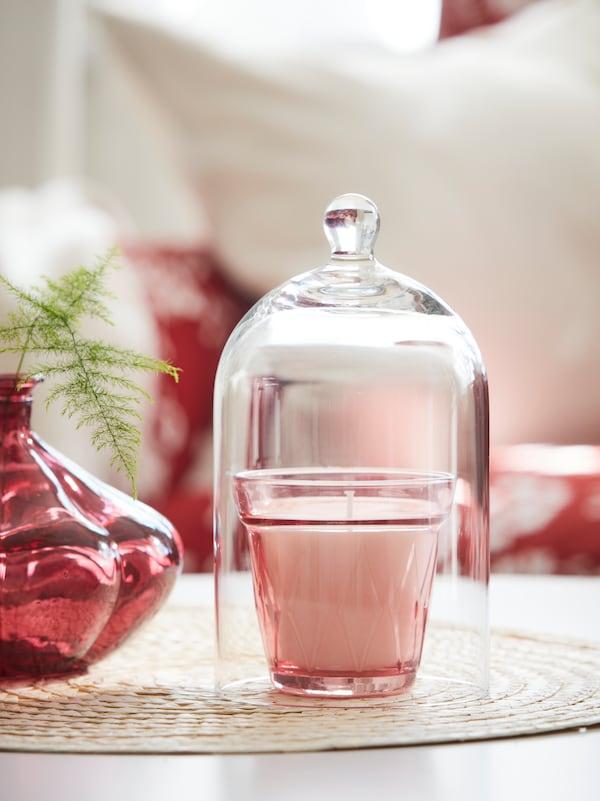Eine Kerze in Rosa befindet sich in einem Kerzenhalter aus Glas und unter einer Glaskuppel auf einem Tischset. Daneben steht eine rote Glasvase mit einem grünen Zweig.