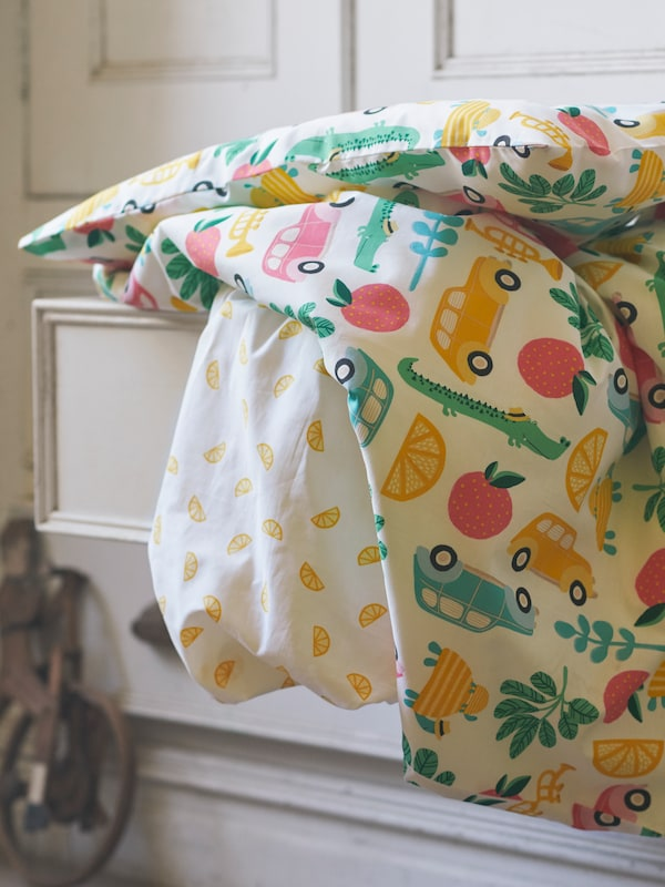 A multicolored, cotton, 3-piece RÖRANDE bed linen set for a crib is draped down from an open drawer in a wardrobe.